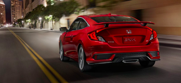 A red new Civic Si Coupe driving down a street.