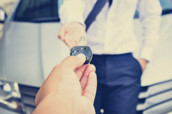 A salesman handing car keys to a person in front of a car.