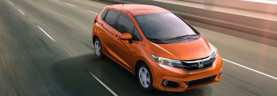 Orange 2019 Honda Fit driving down the highway