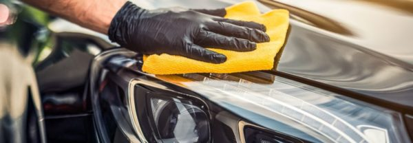 a service man buffing out a scratch on a car